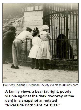 """A family views a bear (at right, poorly visible against the dark doorway of the den) in a snapshot annotated """"Riverside Park Sept. 24 1911."""""""