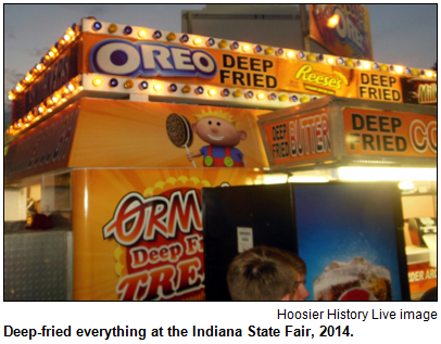 A food stand at the 2014 Indiana State Fair has signs for deep-fried Oreo, deep-fried butter and deep-fried Reeses peanut-butter cups.