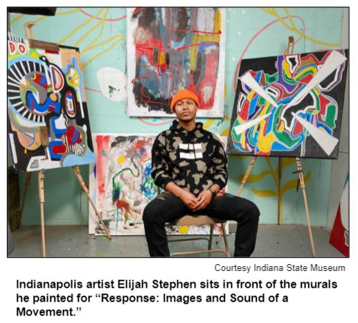 """Indianapolis artist Elijah Stephen sits in front of the murals he painted for """"Response: Images and Sound of a Movement."""" Courtesy Indiana State Museum."""