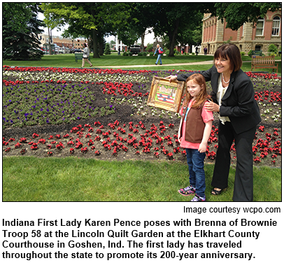 Indiana First Lady Karen Pence poses with Brenna of Brownie Troop 58 at the Lincoln Quilt Garden at the Elkhart County Courthouse in Goshen, Ind. The first lady has traveled throughout the state to promote its 200-year anniversary. Image courtesy wcpo.com.