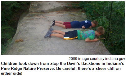 Children look down from atop the Devil's Backbone in Indiana's Pine Ridge Nature Preserve. Be careful; there's a sheer cliff on either side! 2009 image courtesy indiana.gov.